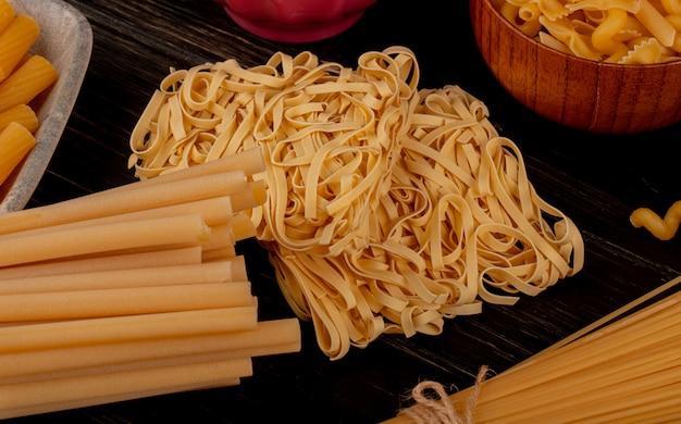 Boczny widok macaronis jako tagliatelle bucatini fusilli i inny na drewnianym stole