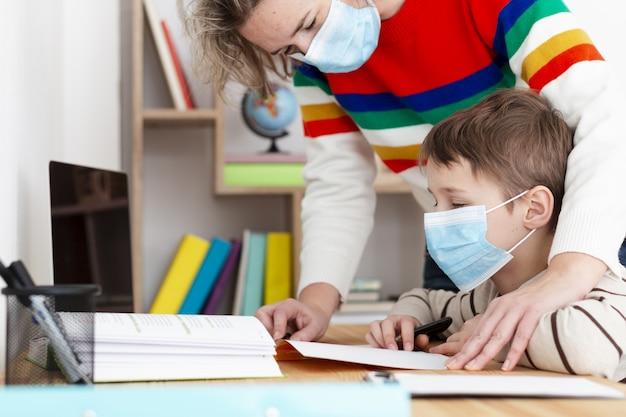 Boczny widok macierzysty pomaga syn z pracą domową podczas gdy będący ubranym medyczną maskę