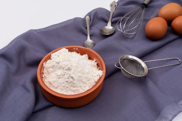 Boczny widok mąka z jajkami na tablecloth na biel powierzchni horyzontalnej