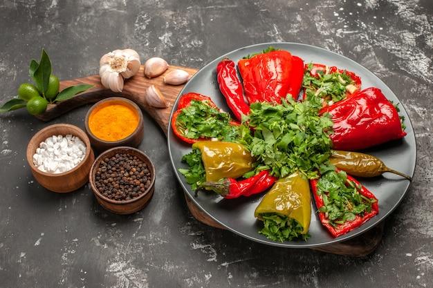 Boczny widok makro talerz papryki talerz papryki z ziołami czosnek przyprawy deska do krojenia