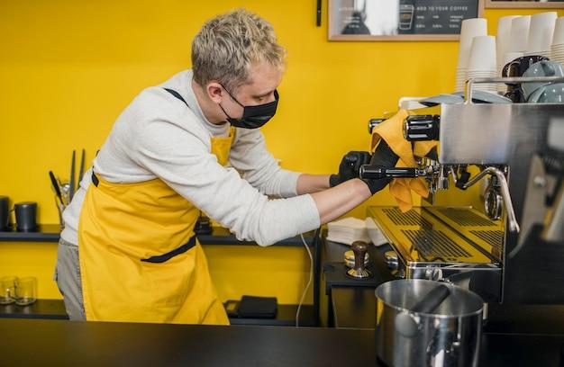 Boczny widok męski barista z medyczną maską czyści ekspres do kawy