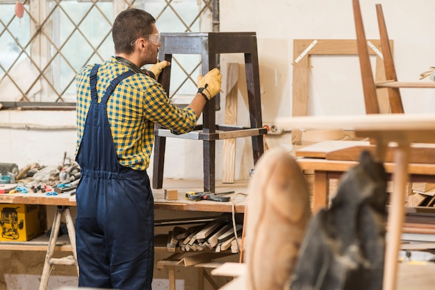 Boczny widok męski cieśla robi drewnianym meblarskim w warsztacie