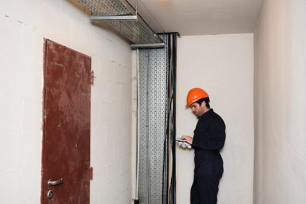 Boczny widok męski elektryk używa telefon komórkowego przy pracą
