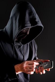 Boczny widok męski hackera mienia smartphone i kędziorek