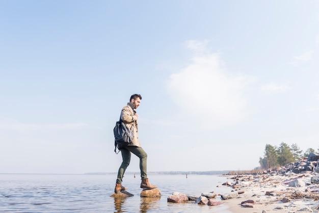 Boczny widok męski podróżnik z jego plecak pozycją na kamieniach w jeziorze