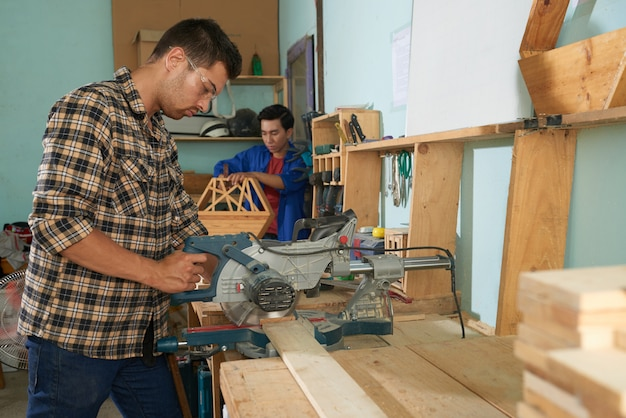 Boczny widok mężczyzna piłuje drewno w szalunku warsztacie w szkockiej kraty koszula