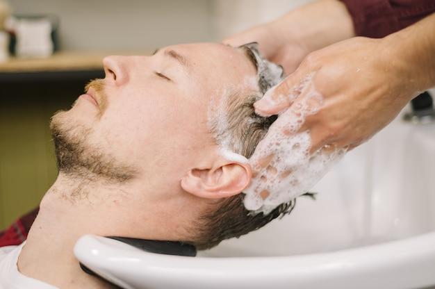 Boczny widok mężczyzna płuczkowy włosy przy fryzjera męskiego sklepem