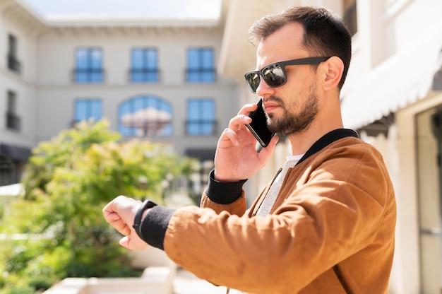 Boczny widok mężczyzna sprawdza czas z okularami przeciwsłonecznymi podczas gdy opowiadający na smartphone