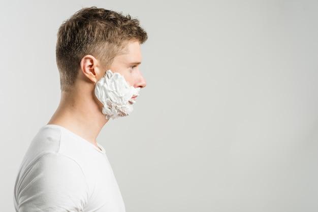 Boczny widok mężczyzna z golenie pianą na jego policzkach odizolowywających nad szarym tłem