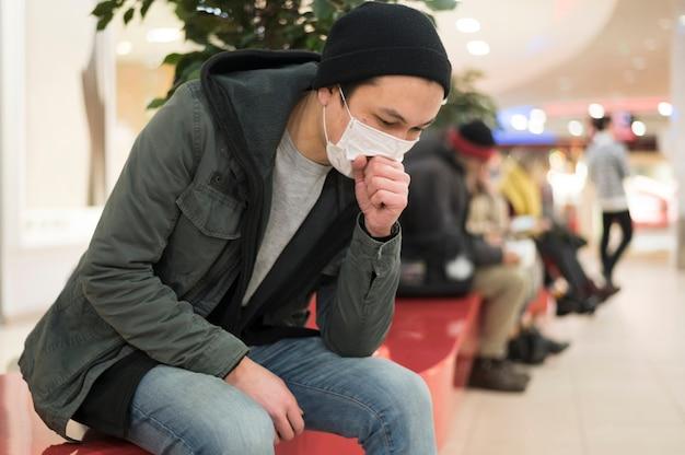Boczny widok mężczyzna z kaskuje medyczną maską podczas gdy przy centrum handlowym