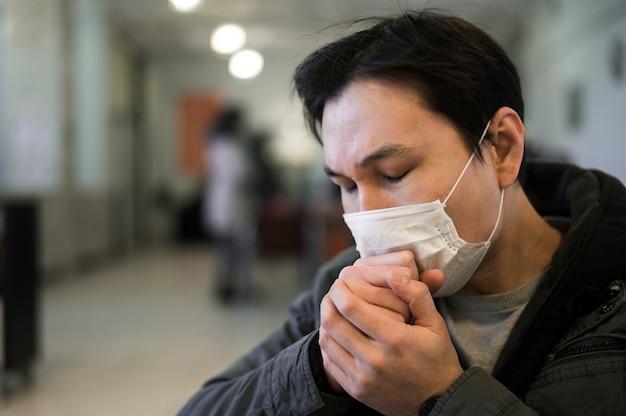 Boczny widok mężczyzna z medyczną maską kaszle