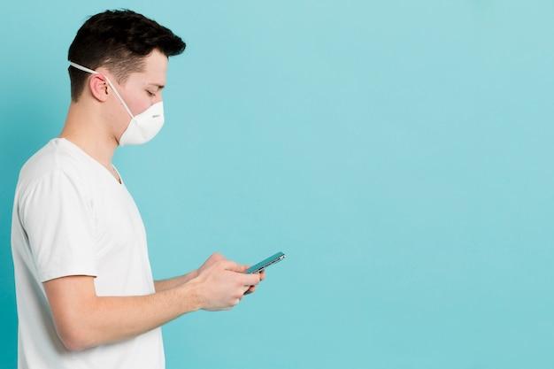 Boczny widok mężczyzna z medycznym maskowym przyglądającym up koronawirusem na smartphone