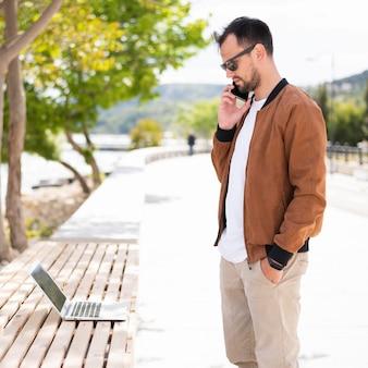 Boczny widok mężczyzna z smartphone outside i laptopem