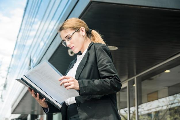 Boczny widok młoda bizneswoman pozycja pod korporacyjnym budynkiem czyta dokument