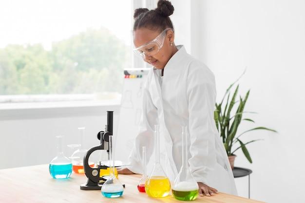 Boczny widok młoda dziewczyna naukowiec patrzeje mikroskop w lab żakiecie