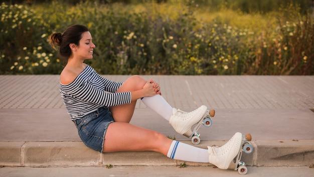 Boczny widok młoda kobieta jest ubranym rolkowej łyżwy rozciąga jej nogę