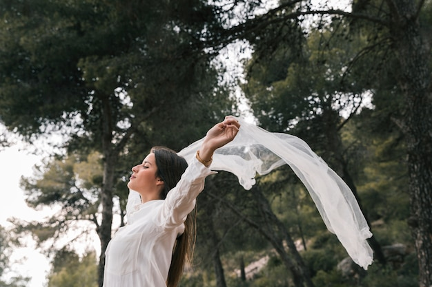 Boczny widok młoda kobieta podnosi jej ręki lata szalika i cieszy się świeże powietrze w lesie