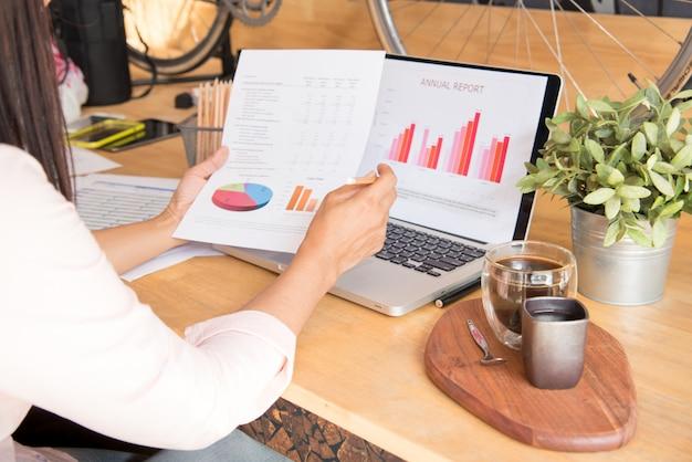 Boczny widok młoda kobieta pracująca używa laptop i czytelniczego sprawozdania rocznego dokument przy pracą. wyświetl raport sprzedaży na notebooku.