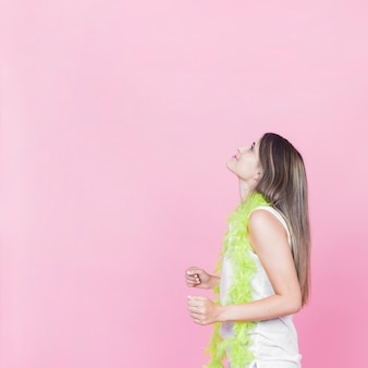 Boczny widok młoda kobieta taniec na różowym tle