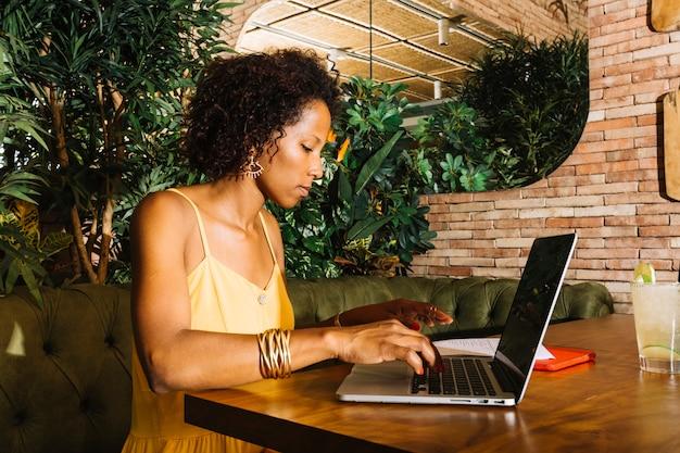 Boczny widok młoda kobieta używa laptop na drewnianym stole w restauraci
