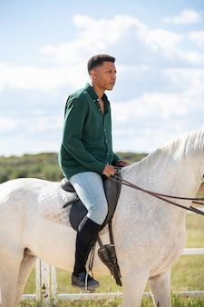 Boczny widok młodego amerykanina afrykańskiego pochodzenia męski patrzeć oddalony podczas gdy siedzący na plecy biały koń na rancho