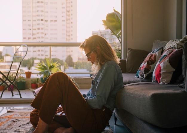 Boczny widok młodej kobiety obsiadanie na dywanowym używa laptopie w domu