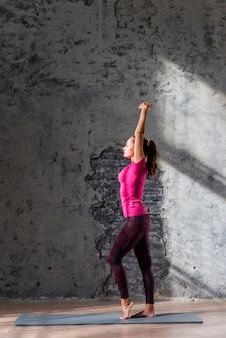 Boczny widok młodej kobiety rozciąganie na ćwiczenie macie przeciw starej szarości ścianie