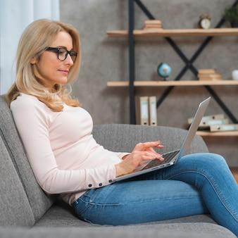 Boczny widok młody blondynki kobiety obsiadanie na kanapie pisać na maszynie nad laptopem