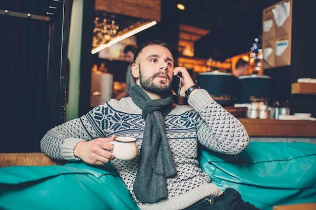 Boczny widok młody brodaty mężczyzna, ubierająca incasual odzież, siedzi przy round drewnianym stołem w kawiarni z nowożytnym wnętrzem i trzyma smartphone.