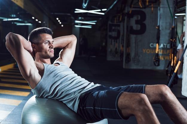 Boczny widok młody człowiek ćwiczy na sprawności fizycznej piłce