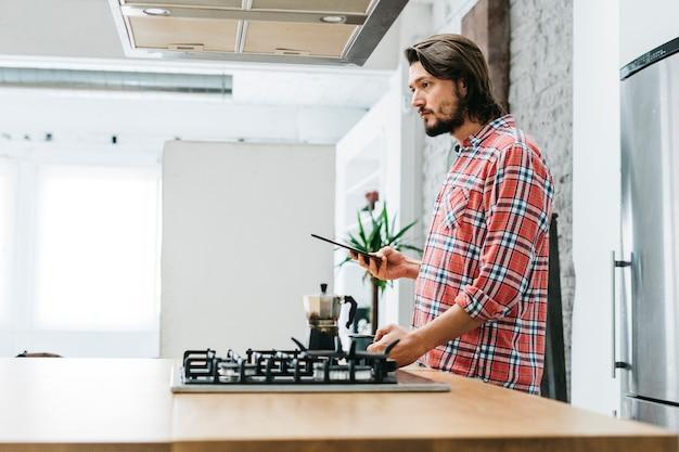Boczny widok młody człowiek pozycja w kuchni trzyma mądrze telefon