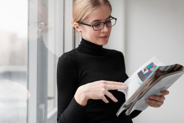 Boczny widok młody żeński czytelniczy magazyn