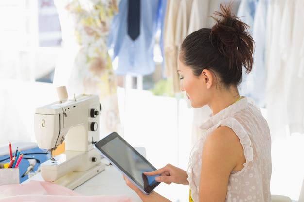 Boczny widok młody żeński projektant mody używa cyfrową pastylkę w studiu