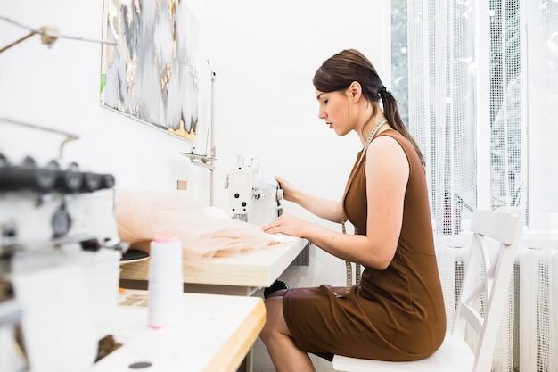 Boczny widok młody żeński projektant pracuje na szwalnej maszynie