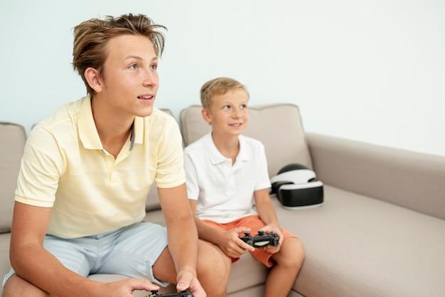 Boczny widok nastolatek i dzieciaka bawić się