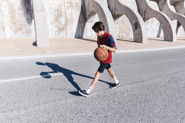 Boczny widok nastoletni chłopak bawić się koszykówkę blisko otaczającej ściany
