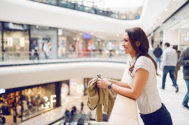 Boczny widok opiera na poręczu i trzyma kurtkę i mądrze telefon atrakcyjna brunetka podczas gdy cieszący się jej czas w zakupy centrum handlowym.