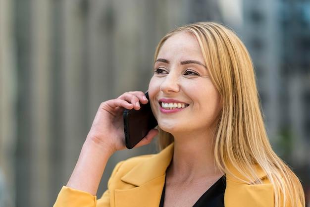Boczny widok opowiada na smartphone biznesowa kobieta