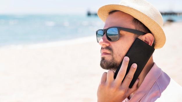 Boczny widok opowiada na smartphone przy plażą mężczyzna