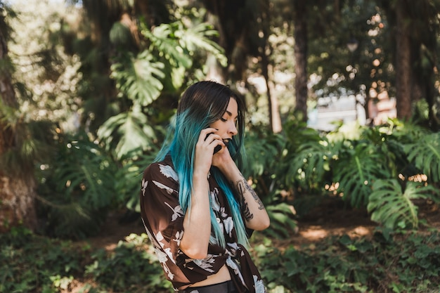 Boczny widok opowiada na telefonie komórkowym w parku młoda kobieta