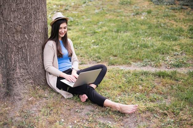 Boczny widok outdoors pracuje na laptopie kobieta