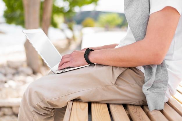 Boczny widok outdoors pracuje na laptopie mężczyzna