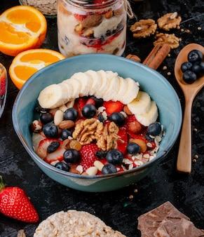 Boczny widok owsianka owsianka z truskawek jagod bananami suszył owoc i dokrętki w ceramicznym pucharze na stole