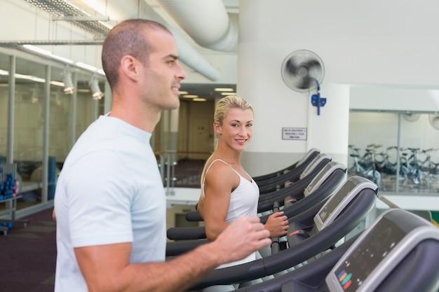 Boczny widok para bieg na karuzelach przy gym