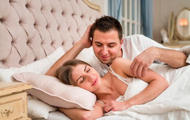 Boczny widok para jest romantyczny w łóżku