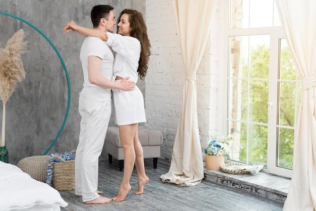 Boczny widok para w domu obejmował obok okno