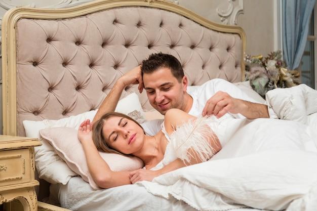 Boczny widok para w łóżku z piórkiem