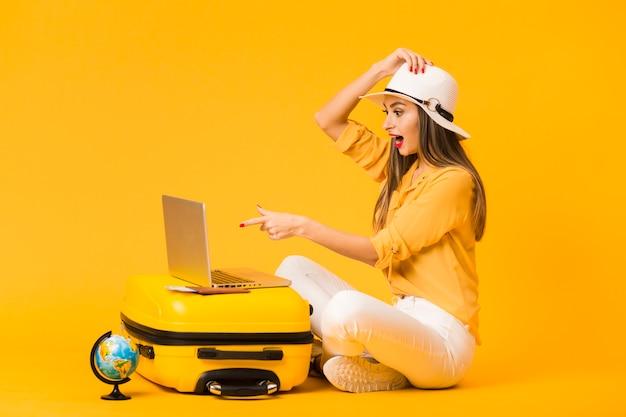 Boczny widok patrzeje laptop na górze bagażu zdziwiona kobieta