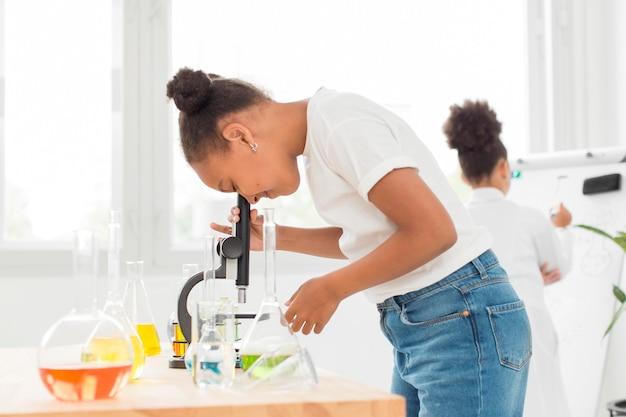 Boczny widok patrzeje przez mikroskopu dziewczyna