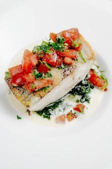 Boczny widok piec seabass z pomidorami na biel powierzchni